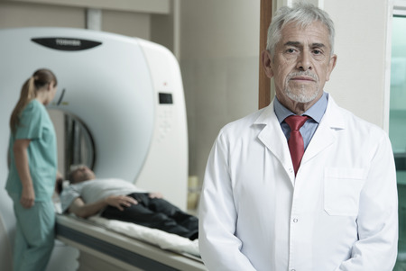 Worried expert senior male doctor awaiting his patient to undergo a CT scan, with her assistant helping .