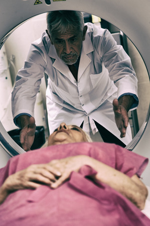 computerised: Senior male doctor examining woman in 70s with CT scanner. Stock Photo
