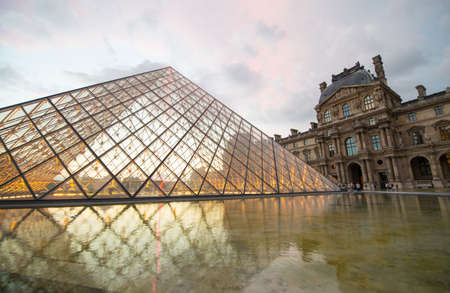 palais: PARIS - JUNE 19: The Louvre museum and the pyramid on June 19, 2014 in Paris, France. The Louvre was once a palace and is now a museum. The pyramid serves as an entrance to the museum