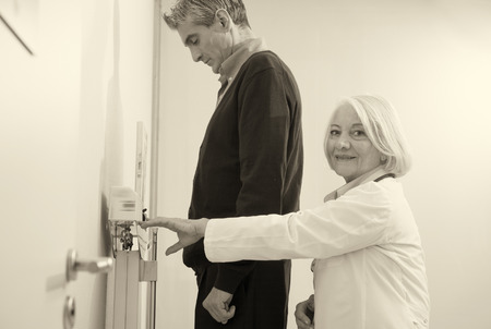 Senior female doctor weighing male patient. photo