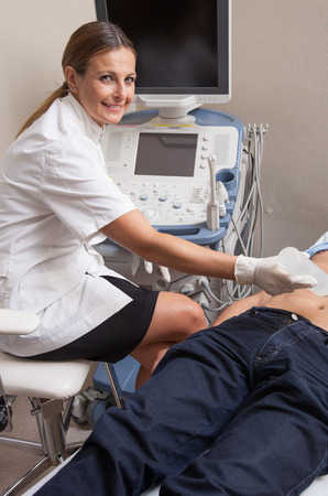 Abdomen echography ultrasound of a senior man. Young female doctor examining patient. photo