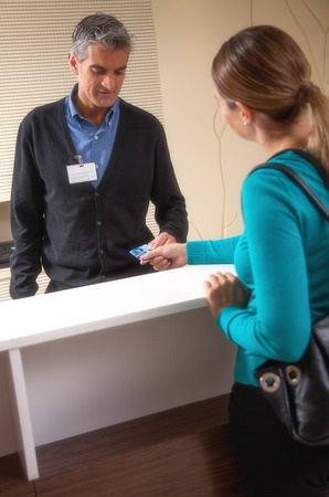 Receptionist and patient discussing about payment at reception desk in hospital. photo