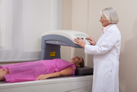 Mature female doctor assisting patient undergoing open mri scan. Zdjęcie Seryjne