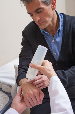 sonography: Woman doctor preparing arm for sonography of tendon sheath. Stock Photo