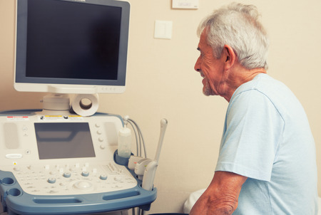 Happy senior male patient looking at medical results on a hospital monitor. photo