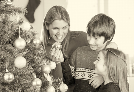 Mother playing with children with Christmas balls and tree. photo