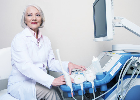 Femme médecin senior souriant lors de la configuration machine à ultrasons. Banque d'images