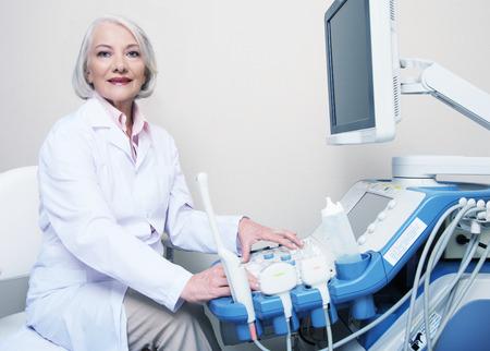 Senior female doctor smiling while setting up ultrasound machine. Stock Photo