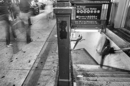 subway entrance: New York City. Subway entrance and stairs at night with moving people. Editorial