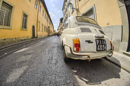 PISA, ITALY - APRIL 14, 2014: Old cinquecento parked in a narrow city street. The Fiat 500 Cinquecento is a city car produced by the Italian manufacturer Fiat between 1957 and 1975.