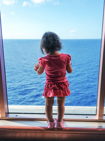 a big ship: Baby looking to the sea from a big ship window.