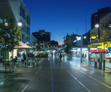 SYDNEY - JULY 21, 2010: Tourists walk along city streets at night. The city attracts more than 10 million people every year.