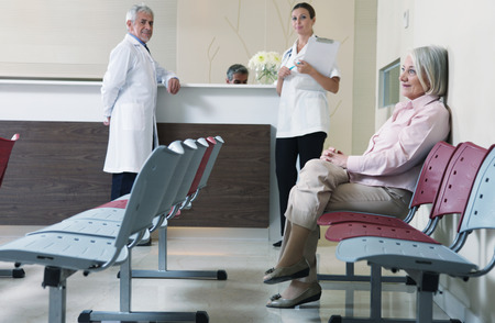 Senior woman patient seated in the hospital waiting room with medical personnel at the desk.