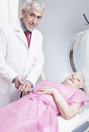 Male doctor reassuring female patient before computed tomography scan. photo