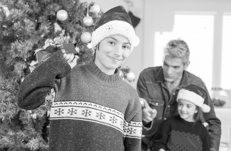 Young boy happy with Christmas gift. Family and tree on background. photo