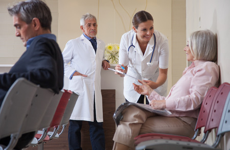 patients: Female doctor talking to patient in waiting room. Stock Photo