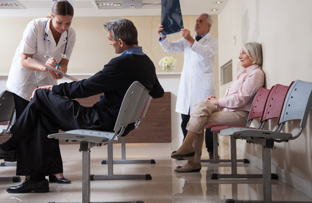 Ärzte Überprüfung Röntgen im Krankenhaus Empfang, während die Menschen im Hintergrund sitzt. Standard-Bild