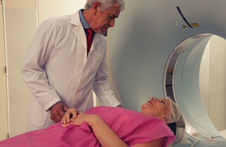computerised: Senior male doctor examining woman in 70s with CT scanner. Computerised tomography  Stock Photo