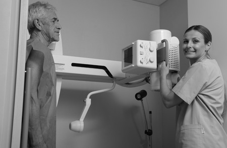 radiotherapy: Smiling female doctor scanning man in 70s with x-ray device.