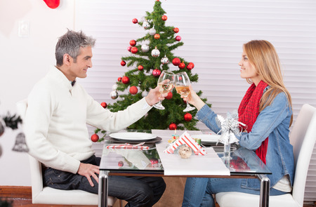 Wife and husband couple drinking champagne at home for Christmas time. photo