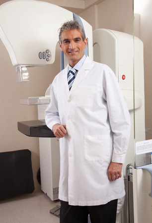 Happy smiling male doctor in the hospital in front of medical machine. photo