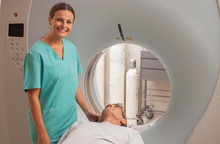 Man undergoing magnetic resonance with reassuring female doctor supervising exam.