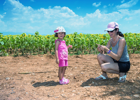 Mother and daughter enjoying outdoor with sunflowers field. photo