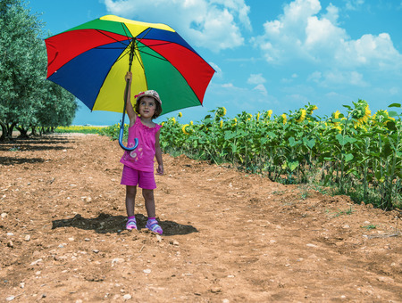 Baby girl enjoying outdoor with colorful umbrella and sunflowers field. photo