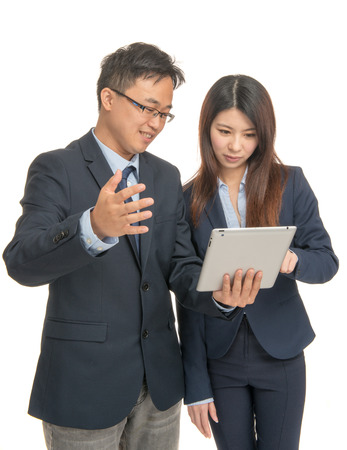 Asian business man and woman discussing company results  on the tablet. Isolated on white. photo