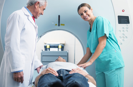 Patient undergoing MRI at open scanner machine. Stock Photo