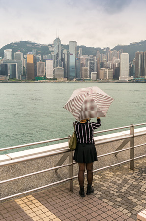 mesmerized: Asian girl with umbrella mesmerized by Hong Kong panorama. Stock Photo