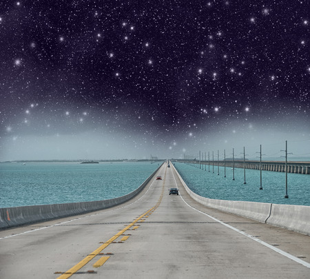 Infinite road to the ocean with stars in the night. photo