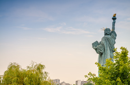 Back view of Statue of Liberty in Paris surrounded by trees.