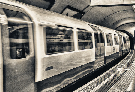 A subway train in motion arriving at a London underground train station