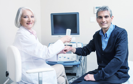 sonography: Wrist sonography. Happy man in 40s undergoing test assisted by mature female doctor. Health concept.