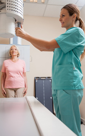 x ray machine: Happy female patient in 60s undergoing x-ray scan. Health concept.