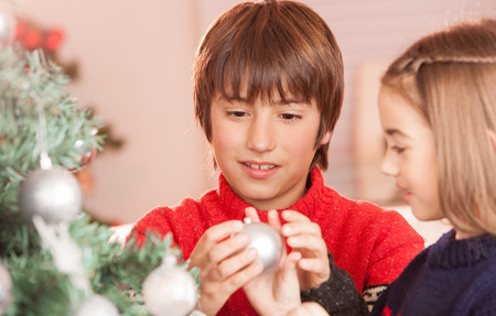 unwrapping: Happy sister and brother celebrating Christmas at home. Children and family concept.