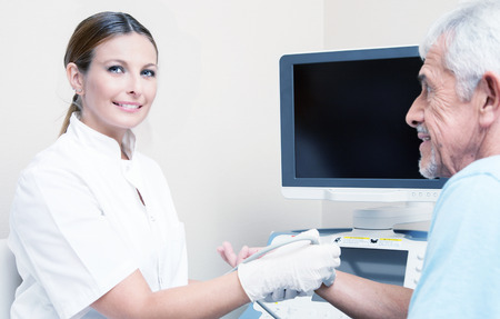 Happy female doctor assisting man patient undergoing wrist echography. Health concept. photo