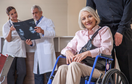 Happy woman in 60s on the wheelchair assisted at the hospital. Health concept. photo