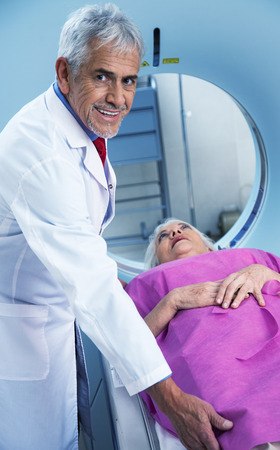 x ray machine: Happy doctor in 70s assisting woman in 60s at mri scan machine. Health concept.