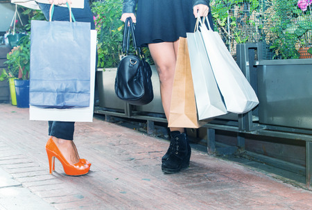personal shopper: Two girls outdoor shopping. Detail on legs and bags.