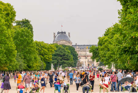 PARIS - JULY 20, 2014: Tourists walk along Tuileries Gardens in Paris. French capital is visited by more than 30 million people annually.
