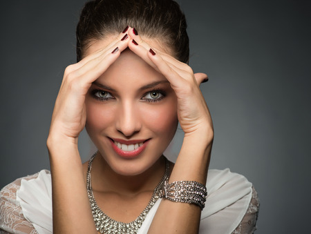 Beautiful woman in 20s framing her face with hands and smiling. Happiness concept. photo