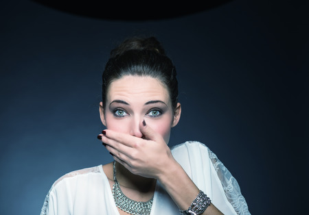 bad breath: Pretty woman covering mouth with hands. Speak no evil concept. Stock Photo