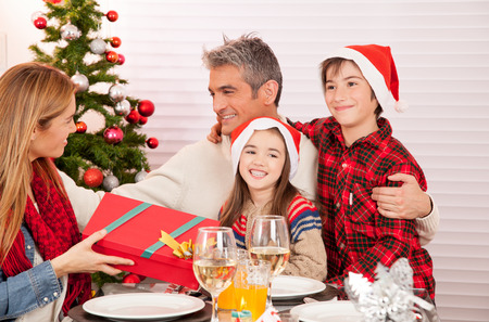 happy family concept: Wife receiving Christmas present from her husband and children. Happy family concept.