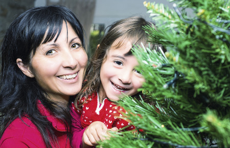 Baby girl with mothe enjoying Christmas tree at home. Family and happiness concept. photo