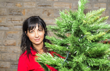 home decorating: Woman in 40s decorating Christmas tree at home. Family and holiday concept.