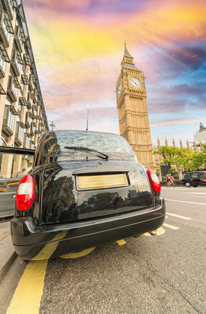 the palace of westminster: Black London cab under Big Ben tower and Westminster Palace. Stock Photo