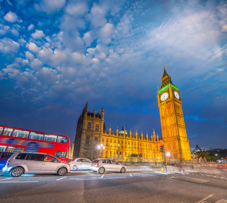 city of westminster: Red Double Decker bus and city traffic at night along Westminster Palace - London. Editorial