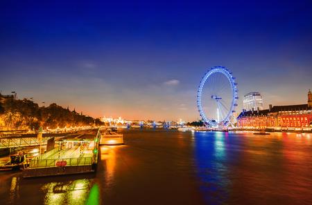 millennium wheel: London night skyline along river Thames. Panoramic wheel, buildings and city lights.